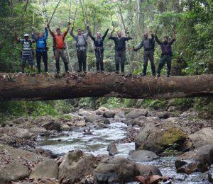 Trekking team stood on a log bridge from a fallen tree in the Darien Gap