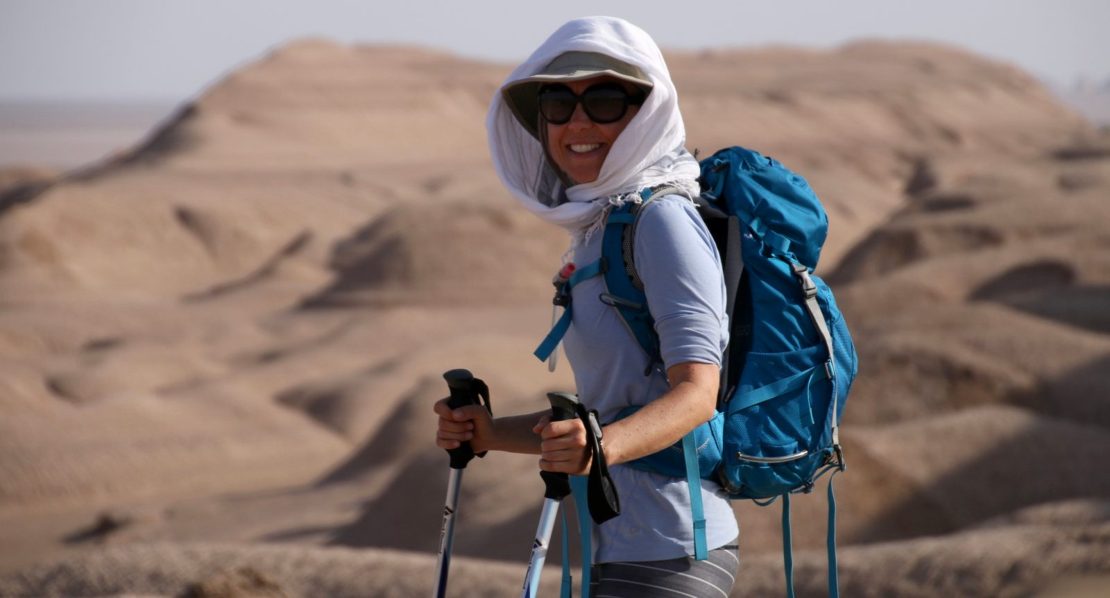 Woman with rucksack and walking poles in Iran's Lut Desert