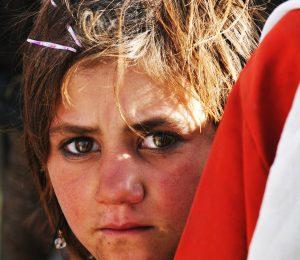 Afghan child peering round, portrait