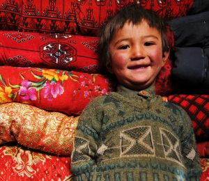 Happy, young Afghan boy by red carpets