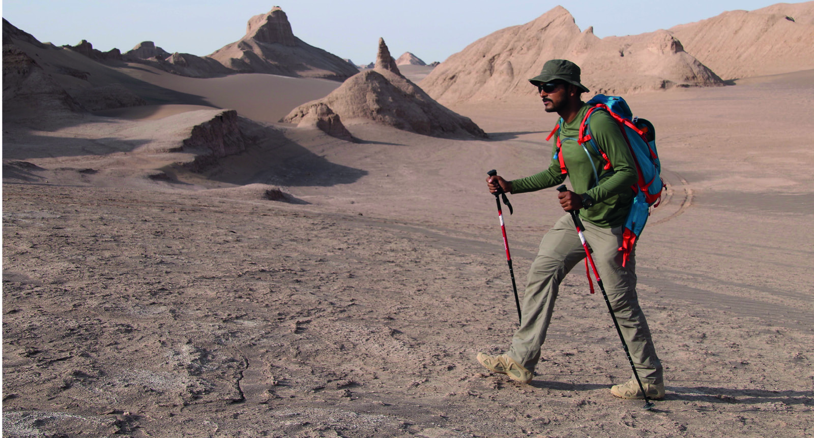Man in Iran's Lut Desert trekking with trekking poles on team expedition  with Secret Compass | Secret Compass