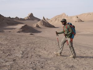 Man in Iran's Lut Desert trekking with trekking poles on team expedition with Secret Compass