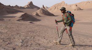 Man in Iran's Lut Desert trekking with trekking poles on team expedition with Secret Compass