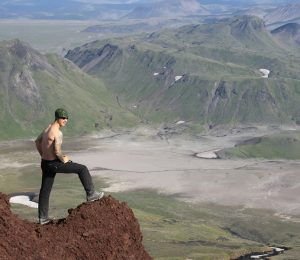 Kamchatka. Trekker over looking the views as he summits the mountain