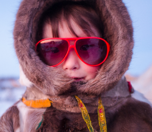 Young Nenets child wearing red sunglasses