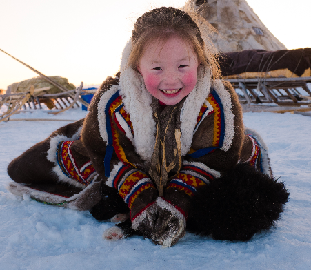 Young Nenets girl playing in the snow
