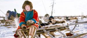 Nenets boy on sledge on reindeer migration, Siberia