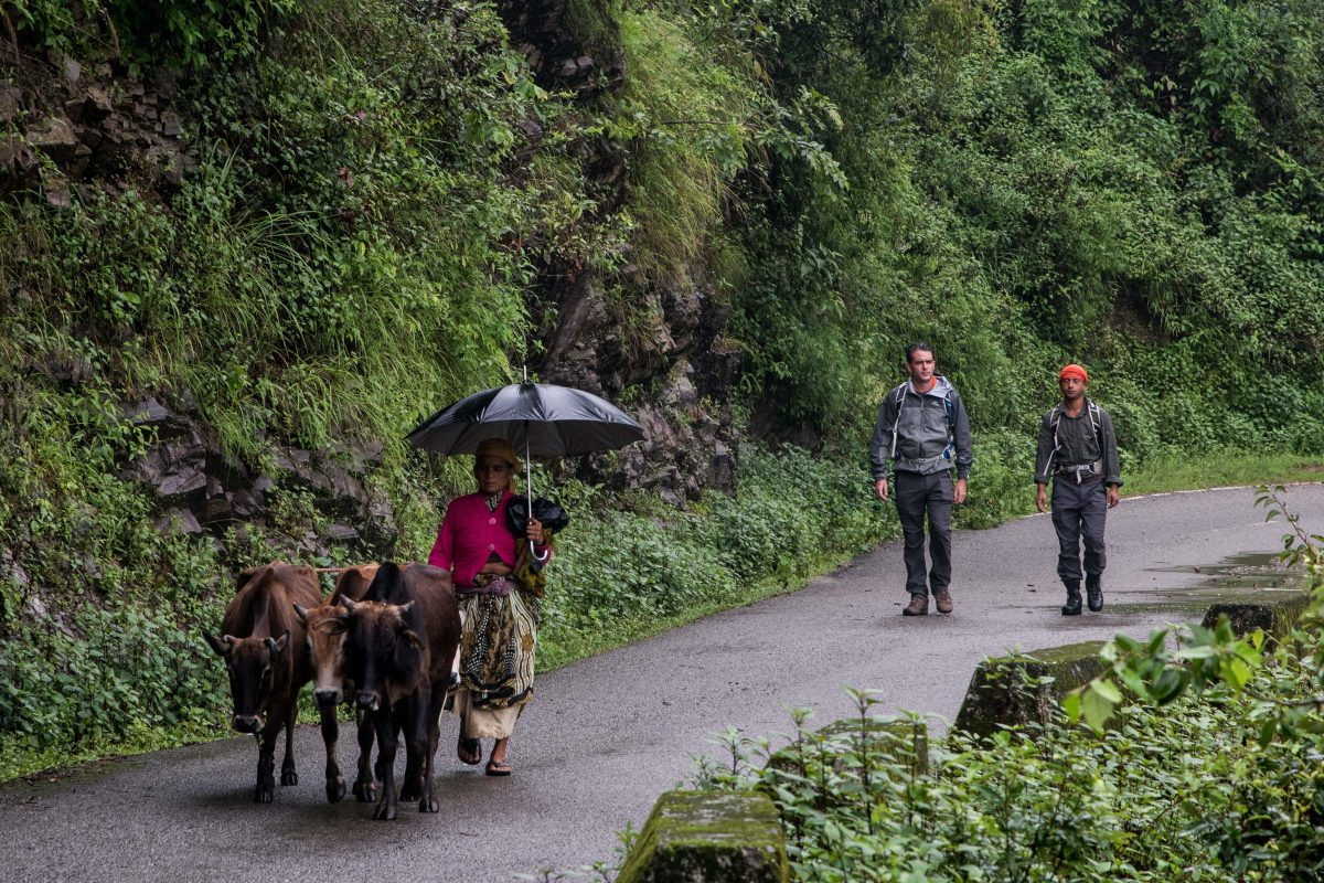 Lev Wood and Binod walk along a mountain road in the Garwal hill