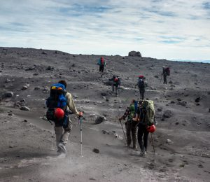 Hiking across an ash field of an active volcano in Russia's Kamchatka