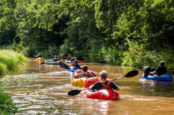 Canoeing down a river on UK adventure academy expedition in Wales