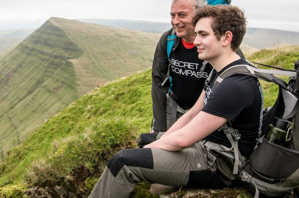 Two teammates take a break to admire the view over the Welsh mountains whilst on the Adventure Academy trip to Wales with Secret Compass