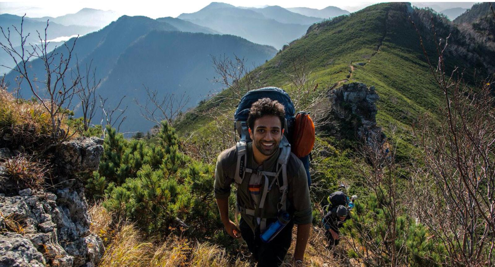 North Korean trek, team member smiles as he climbs up mount Myohyang