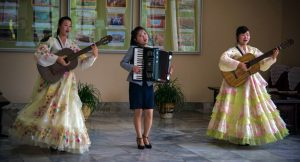 North korean women in traditional dress putting on a performance with guitars and an accordion