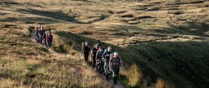 Group of team mates trek along the Brecon Beacons as part of UK adventure academy expedition with Secret Compass