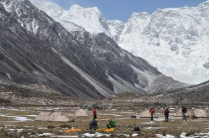 After camping in the valley team mates head towards their summit in the shadow of Gangkhar Puensum.