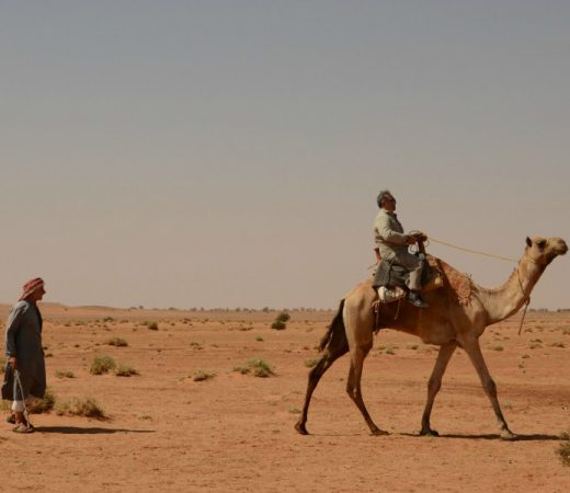 Secret Compass team member rides a camel in the Bayuda desert