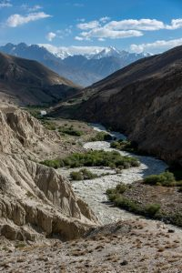 A river bed weaves through the valley between the mountains of the Wakhan Corridor